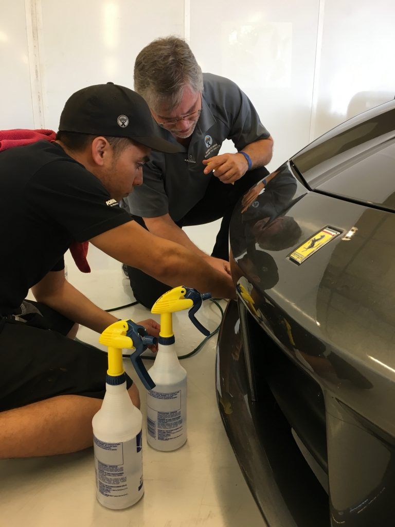 Sunbusters' professionals applying paint protection to black Ferrari